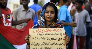 "A demonstrator stands with a sign reading: ""Demands: sack the local authority, disarm militias, protect citizens, cattle, and farmland, and end friction between farmers and shepherds"", during a protest in Central Darfur. Ashraf Shazly/AFP via Getty Images"