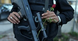 A policeman holds a flower at the site of a bomb attack on a bus transporting Tunisian presidential guards November 25, 2015. EPA Images