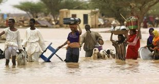 Sudanese people carry their belongings through the flood waters. Isam Al-Haj/AFP via Getty Images