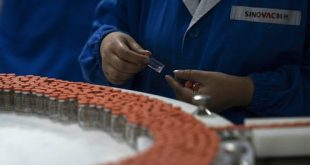 A worker inspects vials of a SARS CoV-2 vaccine for COVID-19 produced by SinoVac at its factory in Beijing on Sept. 24, 2020. (AP Photo/Ng Han Guan)